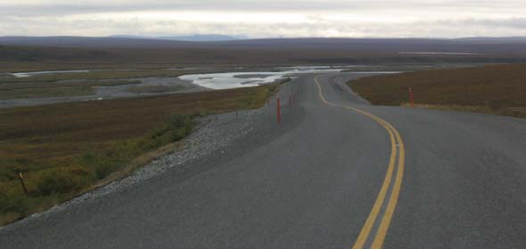 Paved portion of Dalton Highway south of Deadhorse, facing northbound, with small lake along left side of road