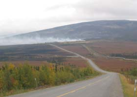 Paved portion of highway, with elevated pipeline on right dropping underground, and wildfire in the distance