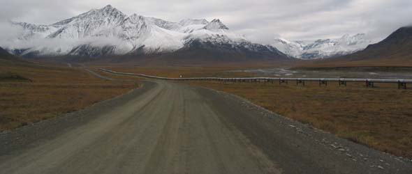 Dalton Highway approaching snow-capped Brooks Range in distance, with pipeline along right side of the road