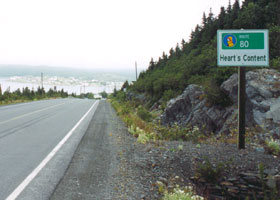 Heart's Content village sign, including small Baccalieu Trail marker, with village far in background