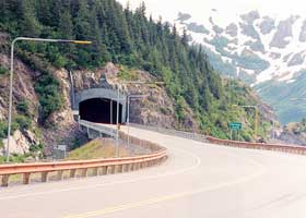 Two-lane highway tunnel under Begich Peak, west portal, with snowplow guides on the approach road